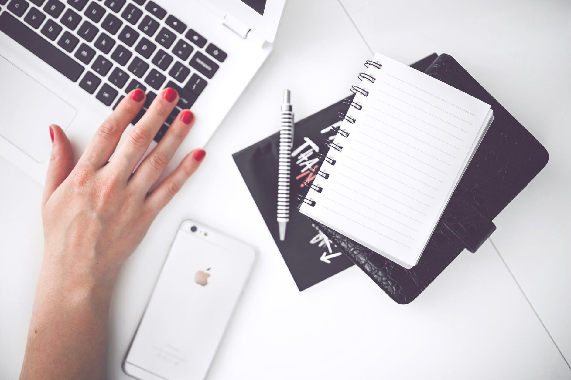 white laptop female hand note pen phone desk
